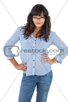 Young woman with her hands on hips and wearing glasses