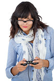 Beautiful woman wearing scarf and glasses playing video games