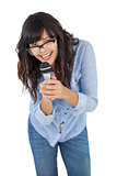 Cute woman wearing glasses and singing with her microphone