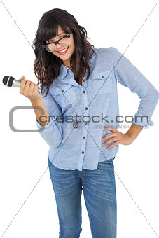 Cute woman with her hand on hip holding microphone