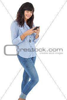 Smiling brunette with her mobile phone texting a message