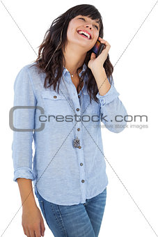 Smiling brunette with her mobile phone calling someone