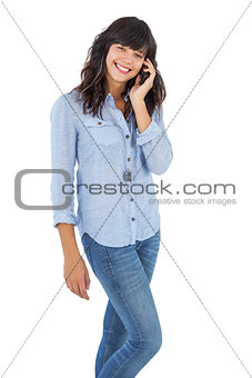 Cheerful brunette with her mobile phone calling someone