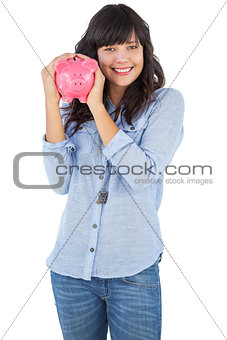 Smiling young woman shaking her piggy bank