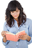 Young woman wearing glasses and reading her book