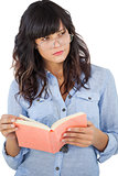 Young woman wearing glasses and thinking about her book
