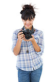 Smiling young woman holding camera for taking picture