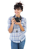 Happy young woman holding camera for taking picture