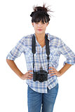 Young woman with camera put hands on her hips