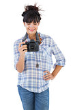 Young woman with hand on her hip taking picture