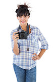Smiling young woman with hand on her hip taking picture