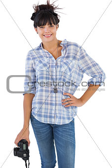 Smiling brunette holding camera with her hand on hip