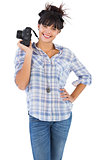 Smiling beautiful woman with her hand on hip and holding camera