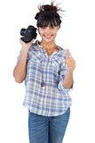 Woman holding camera and giving thumb up