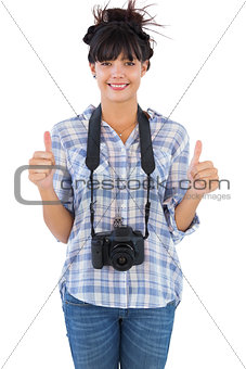 Woman with camera showing  thumbs up