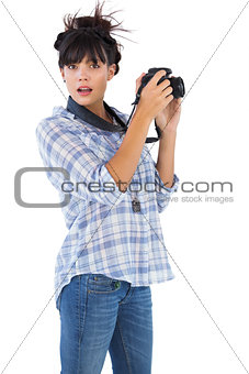 Astonished young woman taking picture with her camera