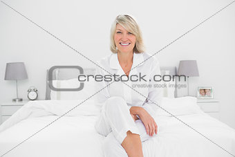 Blonde woman sitting in her bedroom