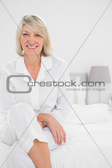 Blonde woman sitting cross legged  in her bedroom