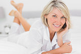 Cheerful woman making a phone call lying on bed