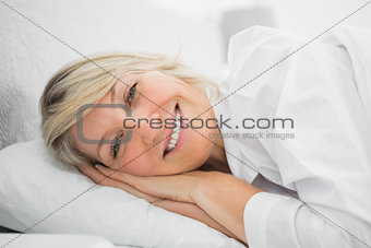 Blonde woman lying in her bed