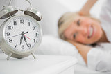 Alarm clock annoying blonde woman in bed