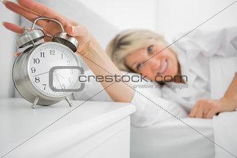 Blonde woman turning off alarm clock