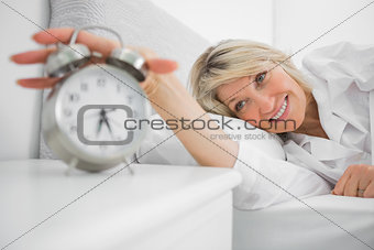 Blonde woman turning off ringing alarm clock