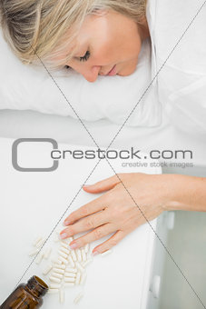 Blonde woman lying motionless after overdosing on tablets