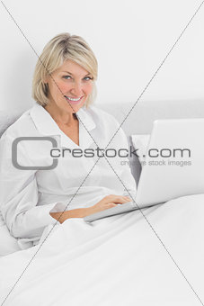 Blonde woman sitting in bed with laptop smiling at camera