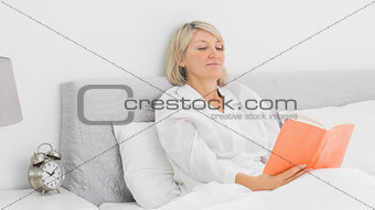 Blonde woman sitting in bed reading
