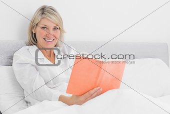 Blonde woman sitting in bed reading smiling at camera