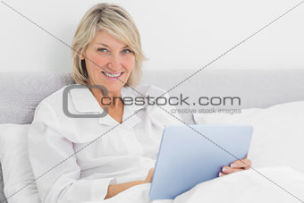 Blonde woman sitting in bed using tablet pc