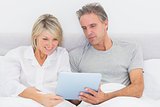 Happy couple using tablet pc in bed