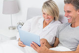 Laughing couple using tablet pc in bed