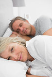 Woman awake as her partner is sleeping in bed