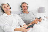 Smiling couple to music on their smartphones