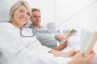 Happy couple reading books in bed