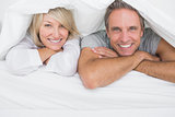 Cheerful couple smiling under the covers at the camera