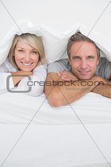 Attractive couple smiling under the covers at the camera