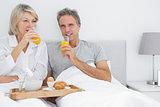 Couple drinking orange juice having breakfast in bed