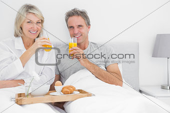 Couple drinking orange juice at breakfast in bed