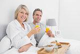 Happy couple having orange juice at breakfast in bed