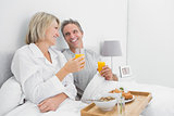 Cheerful couple having orange juice at breakfast in bed