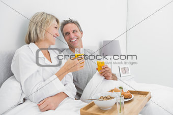 Cheerful couple having orange juice at breakfast in bed