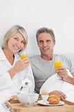 Content couple having orange juice at breakfast in bed