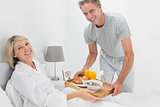 Considerate man giving breakfast in bed to his partner