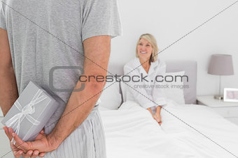 Man hiding present behind his back for partner