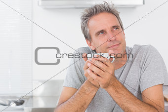 Thoughtful man having coffee in kitchen