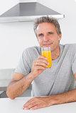 Cheerful man having glass of orange juice in kitchen