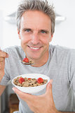 Happy man eating cereal for breakfast